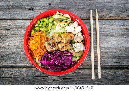 Tofu vegetarian poke bowl over wood table high angle view