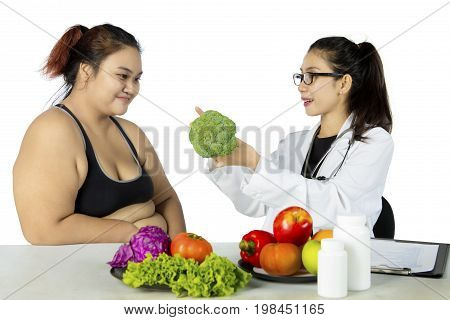 Young female doctor suggesting healthy food while discussion with her patient isolated on white background