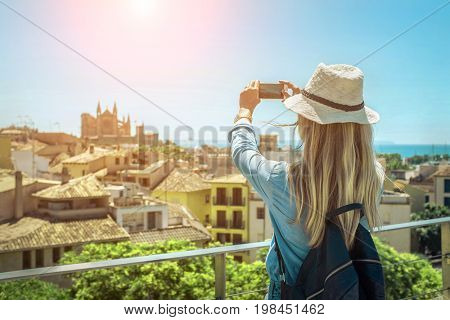 Woman tourist with her phone camera in hands shooting in Palma de Mallorca under sunlight and blue sky in sunny day. One of popular touristic place in Palme de Mallorca.