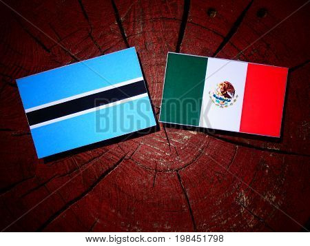 Botswana Flag With Mexican Flag On A Tree Stump Isolated
