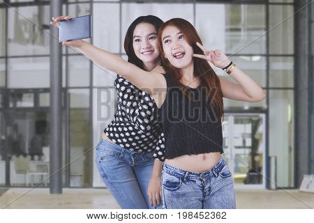Two pretty female students taking selfie photos with a mobile phone while standing in the yard school