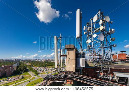 Telecommunication tower with wireless communications systems are including microwave panel antennas fiber optic and power cables of mobile operators are located on the roof and city landscape as background. Outdoor equipment of basic station.