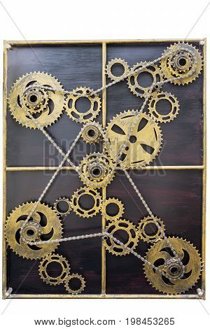 Close up of gold metal cog wheels bound with chains