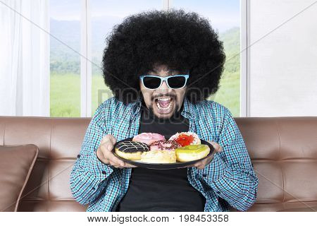 Portrait of a greedy man with curly hair sitting on the sofa while holding a plate of tasty donuts and wearing sun glasses