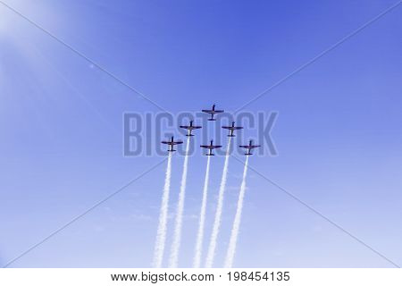 Picture of jet airplanes making formation while doing maneuvers in the blue sky