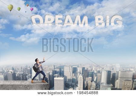 Image of a male college student taking a text of dream big on the sky while standing on the roof