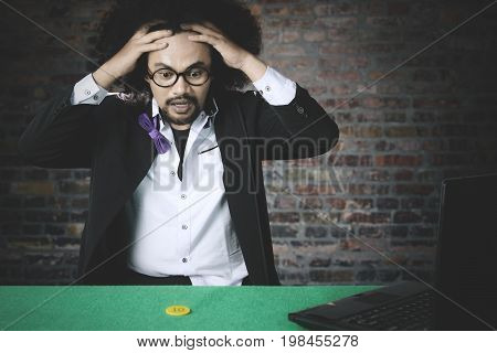 Portrait of Afro man looks frustrated after lose in online poker. Shot with chip and laptop on the table