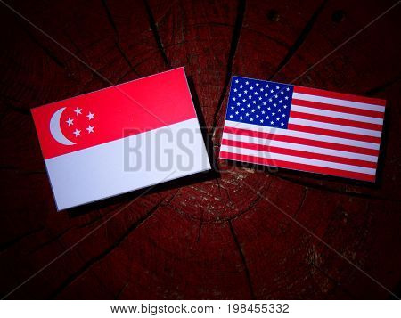 Singaporean Flag With Usa Flag On A Tree Stump Isolated