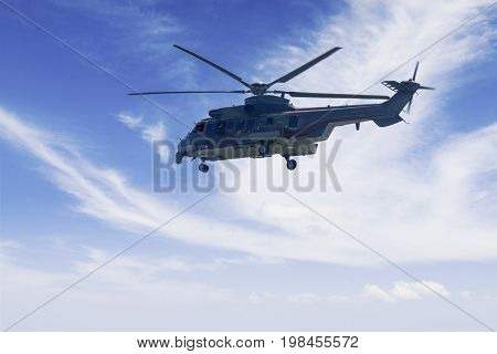 Image of military helicopter is hovering in the blue sky while doing patrols