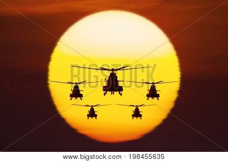 Silhouette of five military helicopters is hovering in the sky with a golden sun shot at sunset time