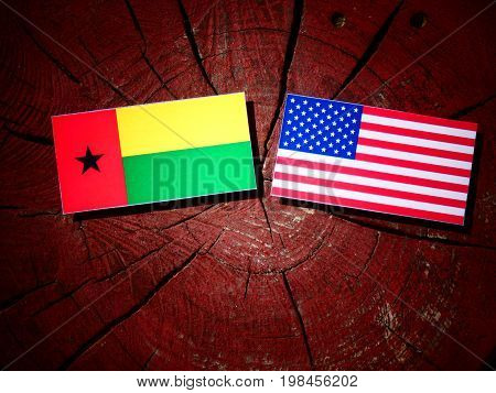 Guinea Bissau Flag With Usa Flag On A Tree Stump Isolated