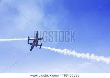 Two jet fighters doing maneuvers while flying in the blue sky