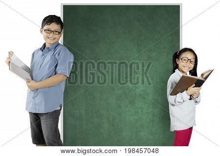 Two nerdy students reading a book while standing near a blank chalkboard isolated on white background