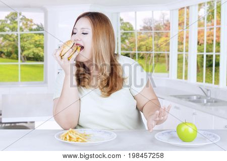 Picture of a young blonde woman choosing to eat hamburger and refusing apple fruit in the kitchen at home