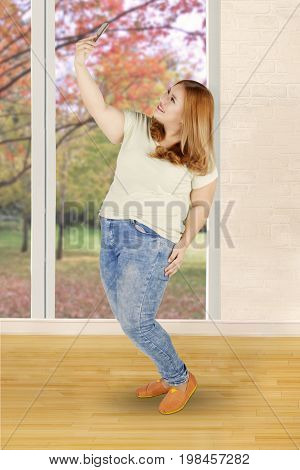 Full length of happy young woman with blonde hair and overweight body taking selfie photo at home. Shot with autumn background on the window
