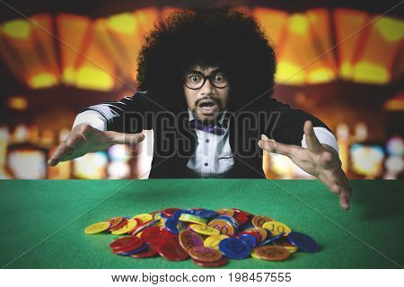 Portrait of young man with curly hair afraid losing chip on the gambling table