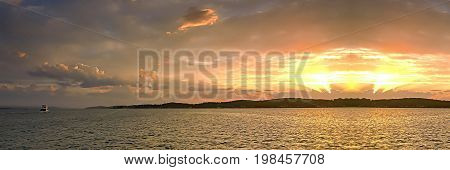 Vibrant golden ocean island sunset seascapethrough cloud and with water reflections and a boat. Photographed at Lake Macquarie New South Wales Australia.