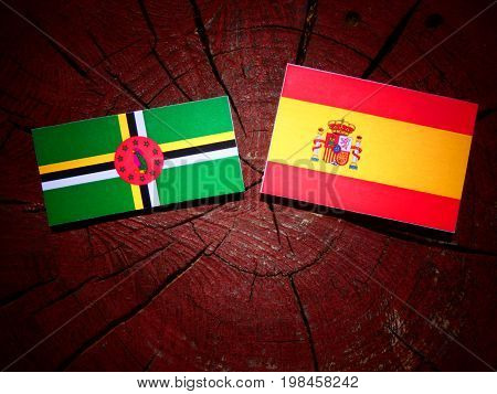 Dominica Flag With Spanish Flag On A Tree Stump Isolated