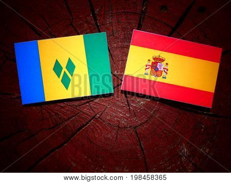 Saint Vincent And The Grenadines Flag With Spanish Flag On A Tree Stump Isolated