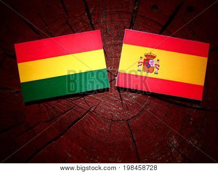Bolivian Flag With Spanish Flag On A Tree Stump Isolated
