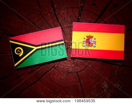 Vanuatu Flag With Spanish Flag On A Tree Stump Isolated