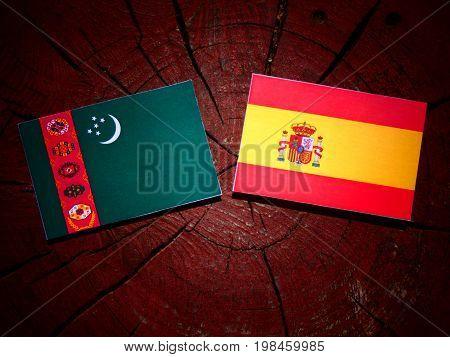 Turkmenistan Flag With Spanish Flag On A Tree Stump Isolated
