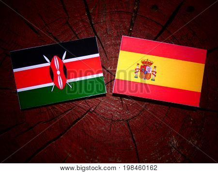 Kenyan Flag With Spanish Flag On A Tree Stump Isolated