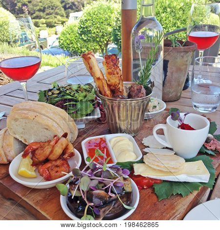 Food platter with cheese crackers bread prawns dips salad microgreens and rose wine served outdoors in New Zealand NZ