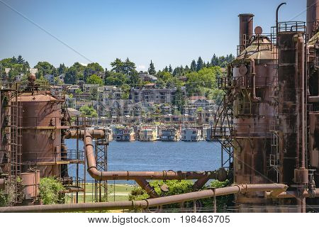 Abandoned Machines And Storage Units In A Gas Industry At Gas Works Park Seattle With Water And Home