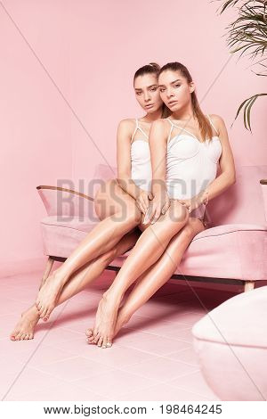 Attractive Twins Sisters Posing Together In Pink Interior.