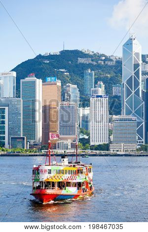 HONG KONG - JULY 10 2017: A colorful Star Ferry approaches a ferry terminal at Tsim Sha Tsui in Hong Kong. The city's iconic Star Ferry carries passengers across Victoria Harbour between Hong Kong Island and Kowloon since 1888.