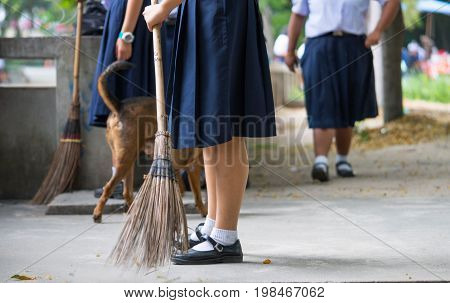 Female students help to sweep the concrete floor with a broom while the dog is walking