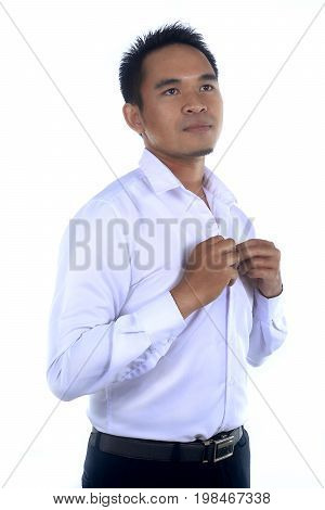 Photo image of a handsome attractive young Asian businessman dressing button up his shirt. Ready to work in formal wear