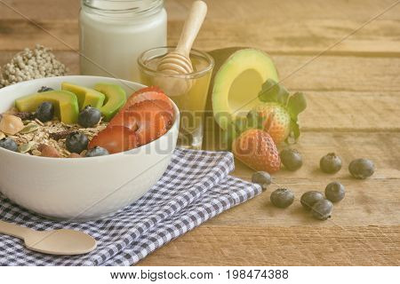 Muesli or granola on white bowl with fresh fruits nuts and cereal. Granola top with blueberries strawberries and avocado served with milk and honey for breakfast.Granola is healthy food for dieting. Start a day with granola for your health.