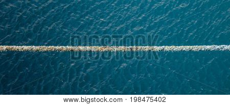 Stretched tight rope over a blue sea background