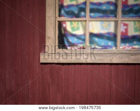 Wooden rustic house window with colorful curtains in a sunny day