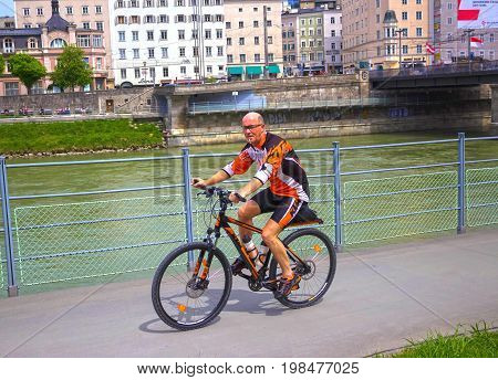 Salzburg, Austria - May 01, 2017: The male cyclist on the embankment in Salzburg, Austria on May 01 2017