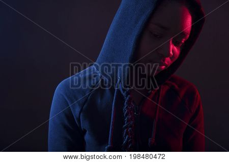 Colorful photo of a pensive and cool woman with dark skin wearing hoodie. Red and blue color studio portrait.
