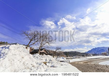 Hakuba mountain range and Lake in the winter with snow on the mountain and blue sky and clouds background in Hakuba Nagano Japan.