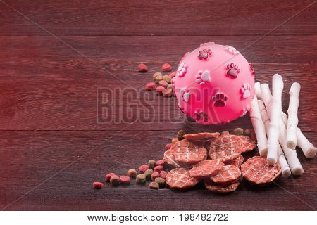 Ball toy for dog and dog snack dog Food dog Chews dog biscuits on a grey wooden table wall background with copy space .