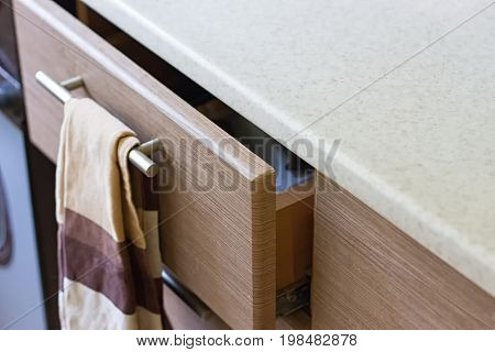 A pull-out kitchen box in the kitchen and a brown towel
