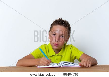 12 years old tween boy sitting at the table with exercise book and looking at the camera. School education.
