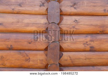 Wall background of round logs house, covered with protective impregnation