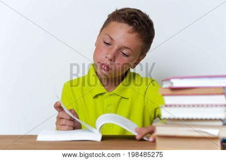 Pensive tween boy sitting at the table and reading a book. Education concept.