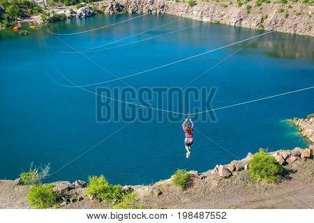 Zipline. The woman in the equipment slides on a steel cable. Trolley Track Over the lake. Extreme and active rest.