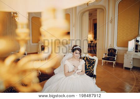 beautiful bride in a magnificent white dress and a crown on his head sitiing on a chair at home
