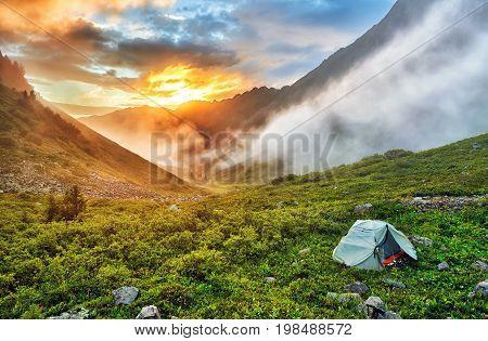 Dawn in Siberian mountains. Tourist tent on of tundra. East Sayan. Buryatia. Russia