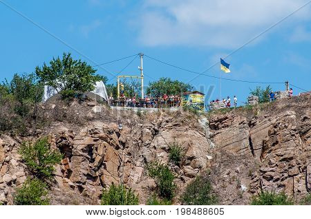 Ukraine Migea - July 30 2017: Zipline. Starting platform on a high rock. The man in the equipment slides on a steel cable. Trolley Track Over the lake. Extreme and active rest.