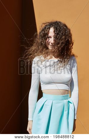 Vertical shot of pretty woman charming eyes and appealing smile dressed in summer clothes relaxing outdoorsenjoying good weather in front orange wall while wind playing in her dark loose curly hair.
