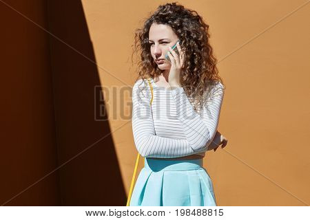 Outdoor shot of unhappy young lady with curly hair having phone conversation with motherdisappointed because of failed exam at universitylistening attentivelylooking aside with serious expression